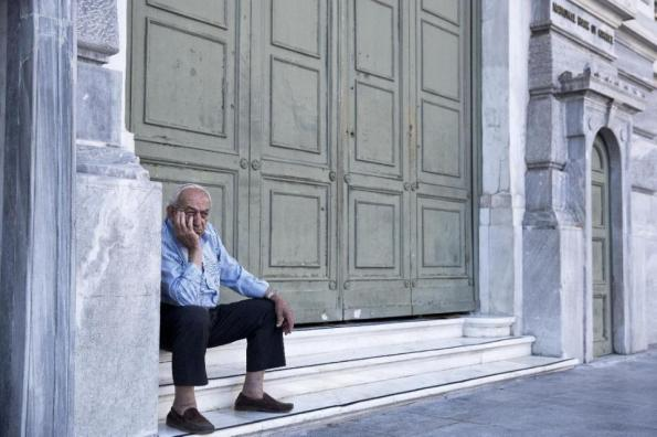 An elderly man waits to receive his pension outside the closed to the public National Bank of Greece headquarters, in Athens, on Tuesday, June 30, 2015. A day after worried elderly Greeks swarmed banks in the hope they would open, the finance ministry said Tuesday morning it would open about 1,000 bank branches across the country for three days this week to allow pensioners without bank cards to make withdrawals. (AP Photo/Petros Giannakouris)
