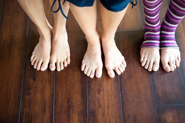 Three women standing on wooden floor