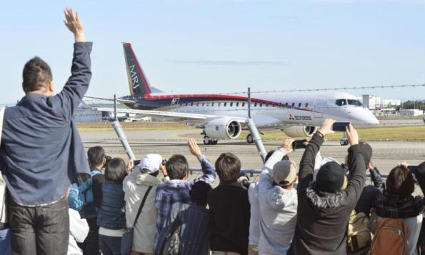 Spectators wave and take photos of Japan's first domestically produced passenger jet, the Mitsubishi Regional Jet (MRJ), taking off from Nagoya Airport in Toyoyama, central Japan, for its first flight Wednesday morning, Nov. 11, 2015. Mitsubishi, a maker of the Zero fighter, took a step toward reclaiming Japan's one-time status as an aviation power Wednesday with the maiden flight of its regional jet. (Yoshiaki Sakamoto/Kyodo News via AP) JAPAN OUT, CREDIT MANDATORY