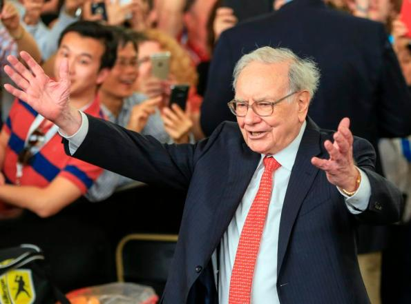 FILE - In this May 3, 2015, file photo, Berkshire Hathaway Chairman and CEO Warren Buffett lifts his arms to greet table tennis prodigy Ariel Hsing, unseen, before briefly playing some table tennis outside the Borsheims jewelry store, a Berkshire Hathaway subsidiary, in Omaha, Neb. Berkshire Hathaway Inc.'s third-quarter profit more than doubled as the completion of the Kraft-Heinz merger boosted the value of its stake in the food giant, the firm announced Friday, Nov. 6, 2015. (AP Photo/Nati Harnik, File)