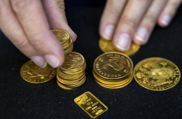 A worker places gold coins on display at Hatton Garden Metals precious metal dealers in London, Britain July 21, 2015. REUTERS/Neil Hall/File Photo