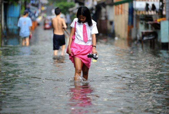 A high school student wades through a flooded street after a heavy rain caused by typhoon Nock-ten in San Juan city, east of Manila on July 26, 2011. One person drowned while thousands fled their flooded homes as a tropical storm hit the Philippines, causing heavy rains and rough seas that disrupted aviation and shipping, officials said. AFP PHOTO/NOEL CELIS (Photo credit should read NOEL CELIS/AFP/Getty Images)
